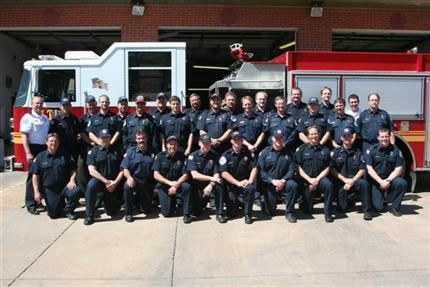 A group photo of emergency staff in front of a fire engine.