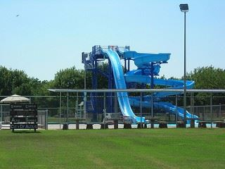 A large blue waterslide rising from a pool.