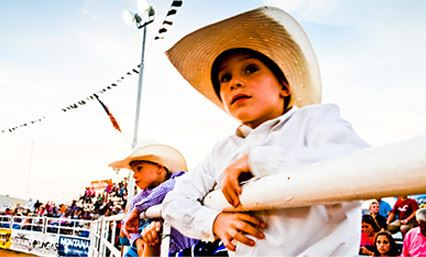 Two boys hanging on a gate in a rodeo arena